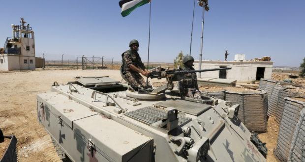 Soldiers stand guard on a tank at the Jordanian-Syrian border, near Mafraq, Jordan