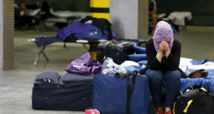 A Syrian woman cries as she sits on a folding bed in a former newspaper printing house used as a refugee registration centre for the German state of Hesse in Neu-Isenburg